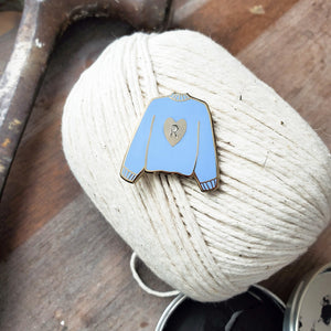 Hand stamped heart sweater enamel pin on a ball of yarn