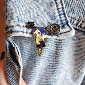 Coraline doll hanging from a button key lapel enamel pin