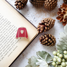 Load image into Gallery viewer, Maroon red hand stamped heart sweater enamel pin with a book and pine cones