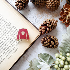 Maroon red hand stamped heart sweater enamel pin with a book and pine cones
