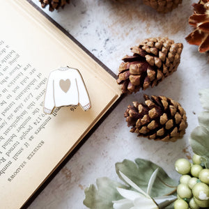 White hand stamped heart sweater enamel pin with a book and pine cones