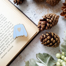 Load image into Gallery viewer, Blue hand stamped heart sweater enamel pin with a book and pine cones