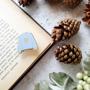 Blue hand stamped heart sweater enamel pin with a book and pine cones