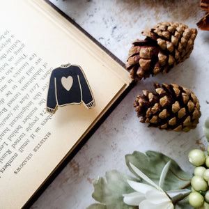 Black hand stamped heart sweater enamel pin with a book and pine cones