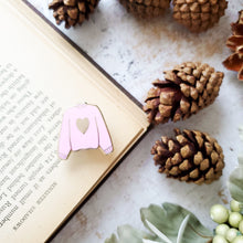 Load image into Gallery viewer, Pink hand stamped heart sweater enamel pin with a book and pine cones