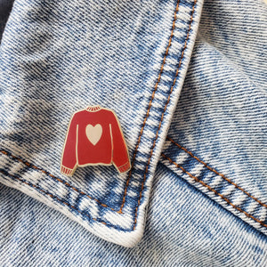 Maroon red hand stamped heart sweater enamel pin on a jean jacket