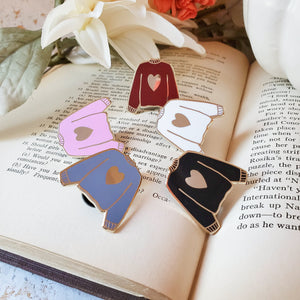 Multi colored hand stamped heart sweater enamel pin on a book