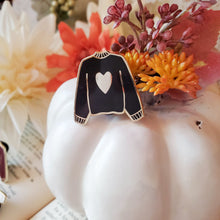 Load image into Gallery viewer, Black hand stamped heart sweater enamel pin on a pumpkin