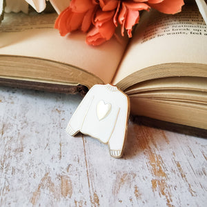 White hand stamped heart sweater enamel pin with a book