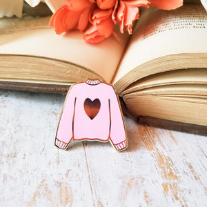 Pink hand stamped heart sweater enamel pin with a book