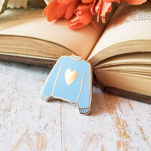 Blue hand stamped heart sweater enamel pin with a book