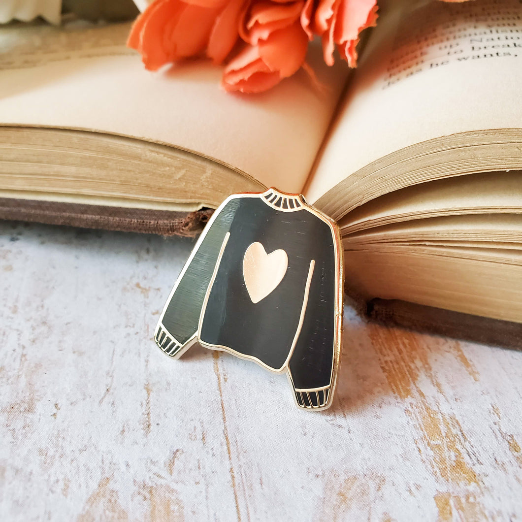 Black hand stamped heart sweater enamel pin with a book