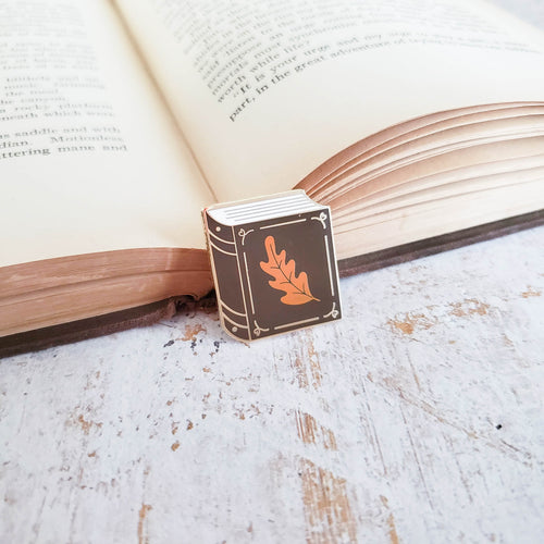 Chocolate brown book with small orange leaf enamel pin resting on a book