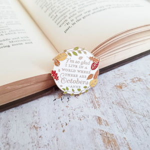 White enamel pin with fall leaf border with Anne of Green Gables quote