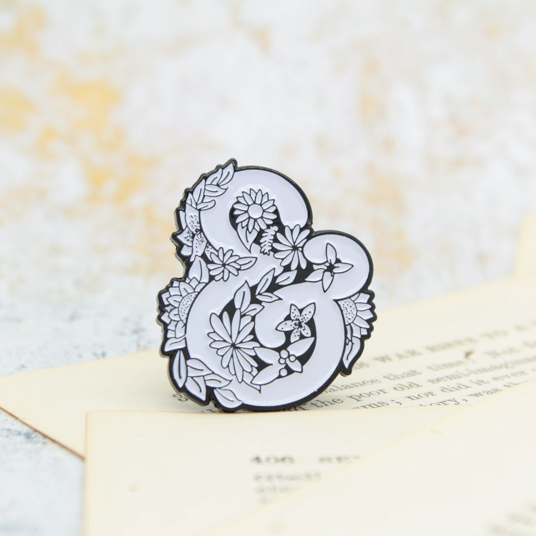Black and white ampersand and symbol surrounded by flowers enamel pin
