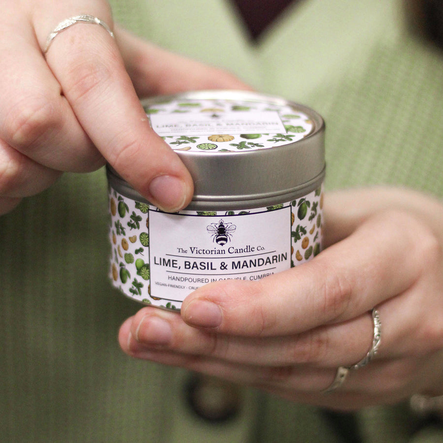 A model presenting a Lime, Basil and Mandarin candle