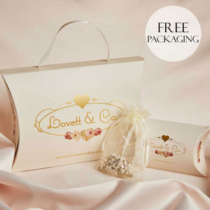 vintage inspired lovett and co cream packaging with gold and flower logo printed. organza bag with flower crystal necklace pictured on a pink silk background