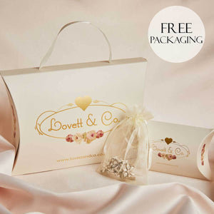 Lovett and co free packaging in cream with gold logo pictured on a pink silk background