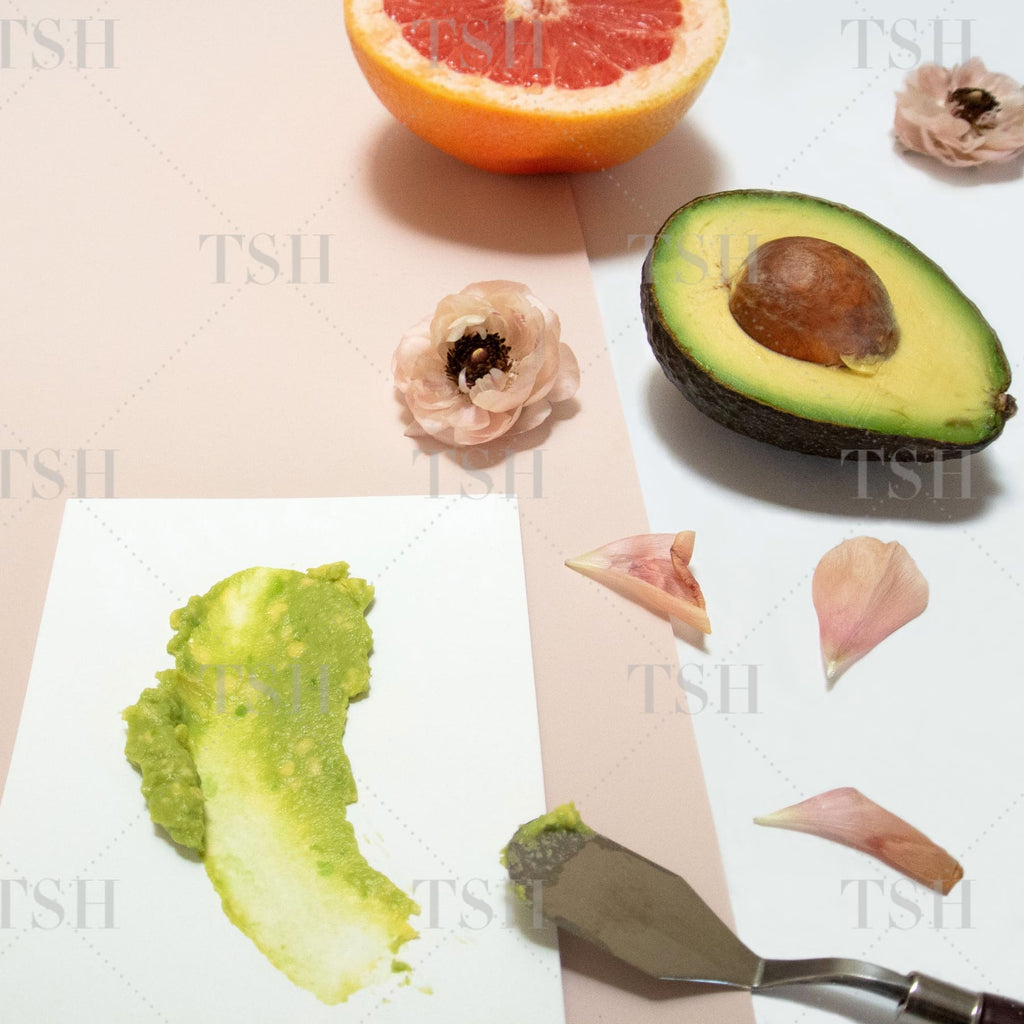 Avocado, grapefruit, and blush flowers on white and blush background.