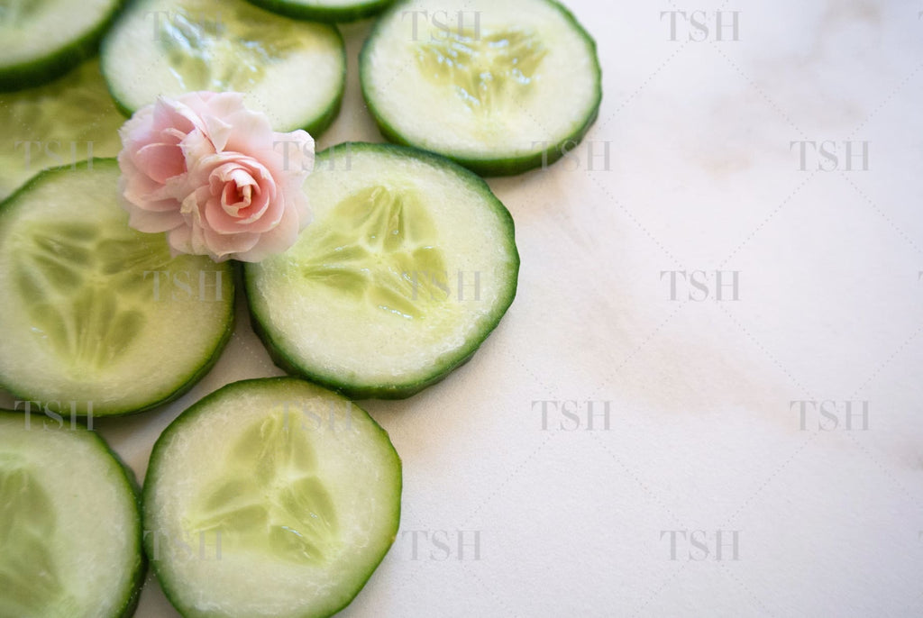 Cucumber slices with pink freesia flowers on marble background.