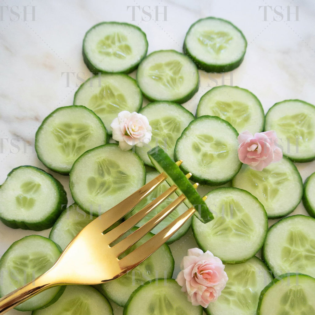 Cucumber slices with gold fork and pink freesia flowers on marble background.