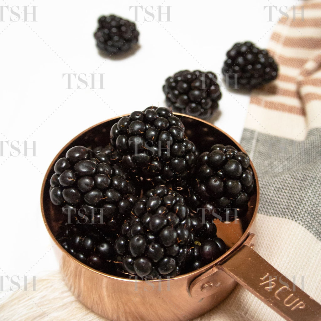 Blackberries in copper measuring cup with neutral and black striped kitchen towel.