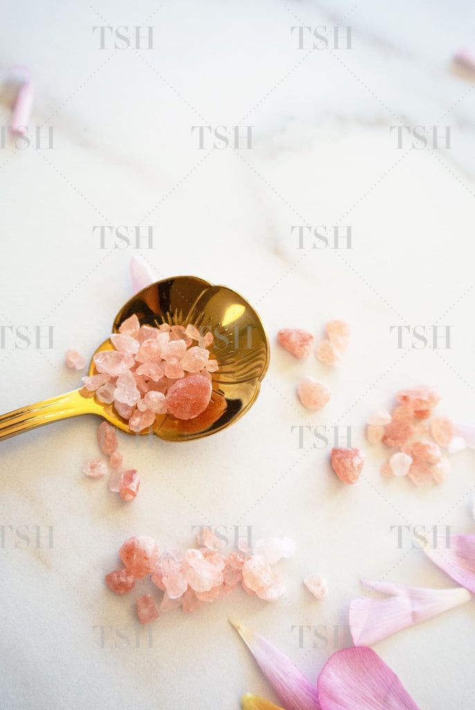 Himalayan Sea Salts on gold spoon with pink flowers petals on marble background.