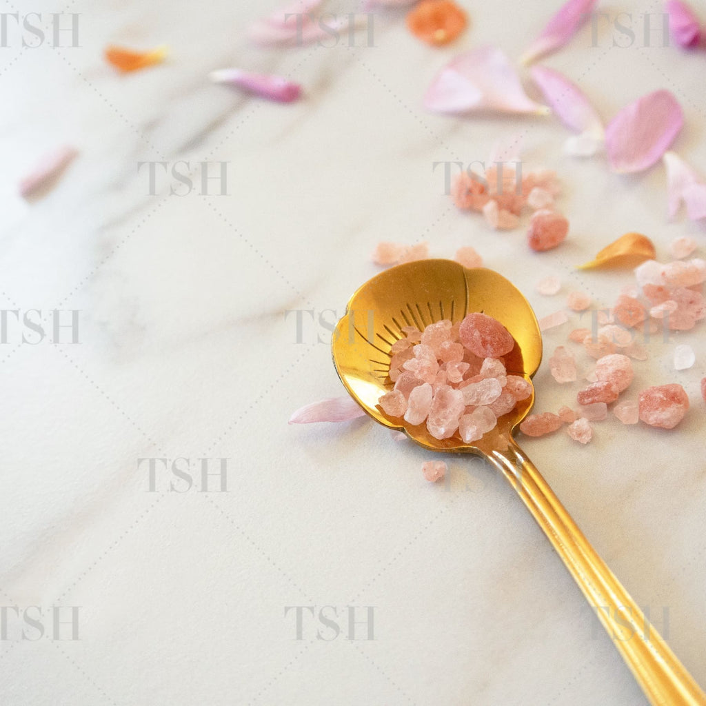 Himalayan Sea Salts on gold spoon with pink and orange flower petals on marble background.