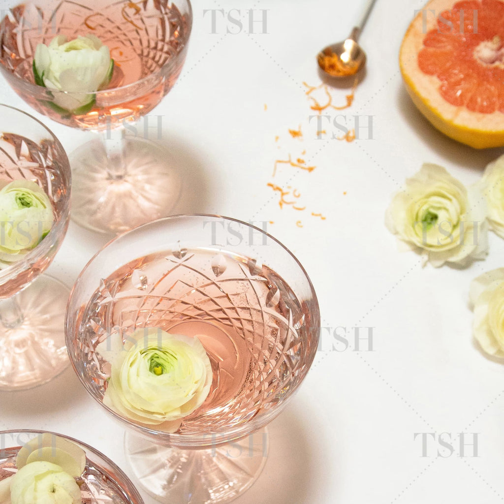 Rosé cocktails in crystal glasses with grapefruit and flowers on white background.