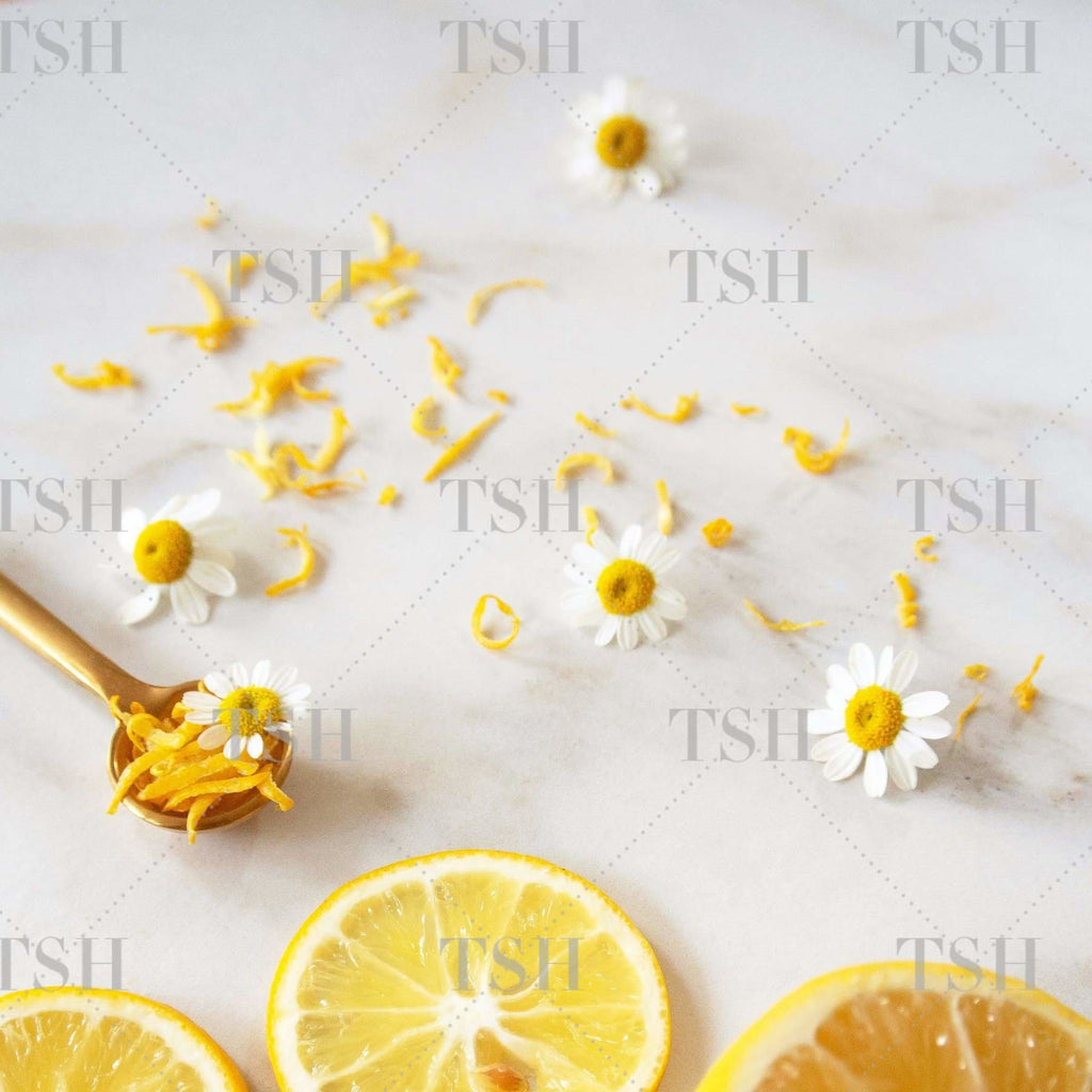Sliced lemons, tossed chamomile flowers and lemon zest with gold spoon on a marble background.