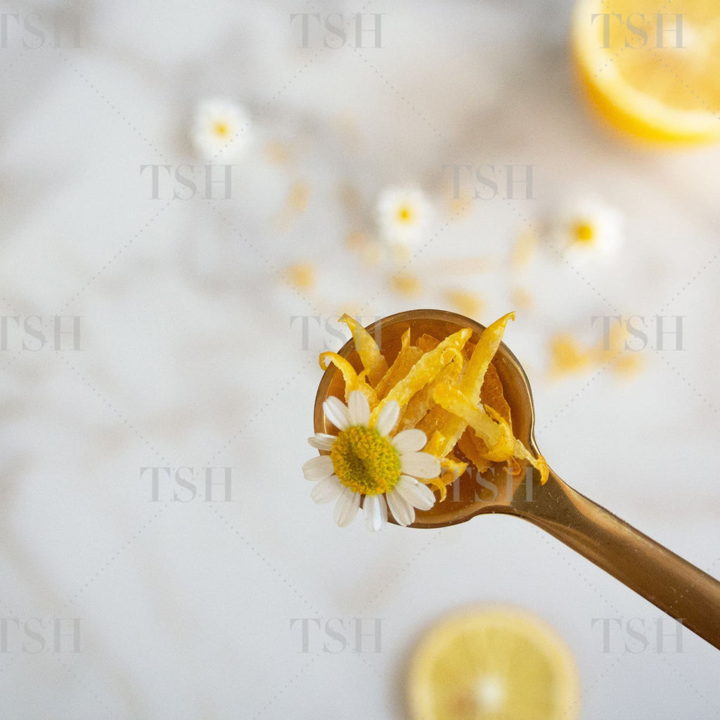 Lemon zest on gold spoon with sliced lemons and tossed chamomile flowers on a marble background.