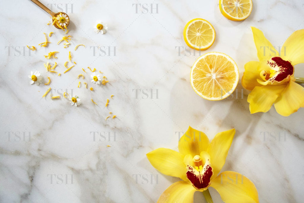 Sliced lemons, tossed chamomile flowers, yellow orchids, and lemon zest with gold spoon on a marble background.