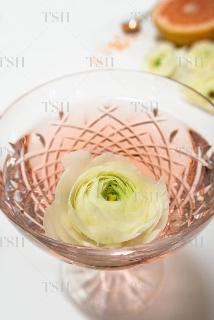 Rosé cocktail in crystal glass with flower garnish on white background.