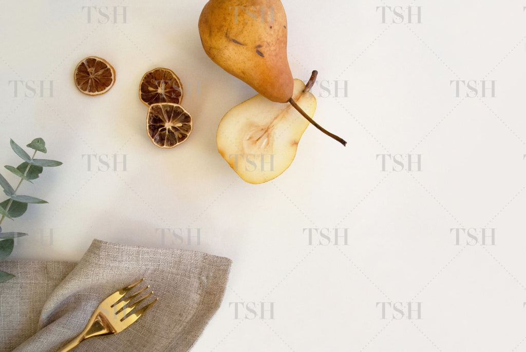 Fall harvest pears, dried citrus, eucalyptus, and linen napkin with gold fork
