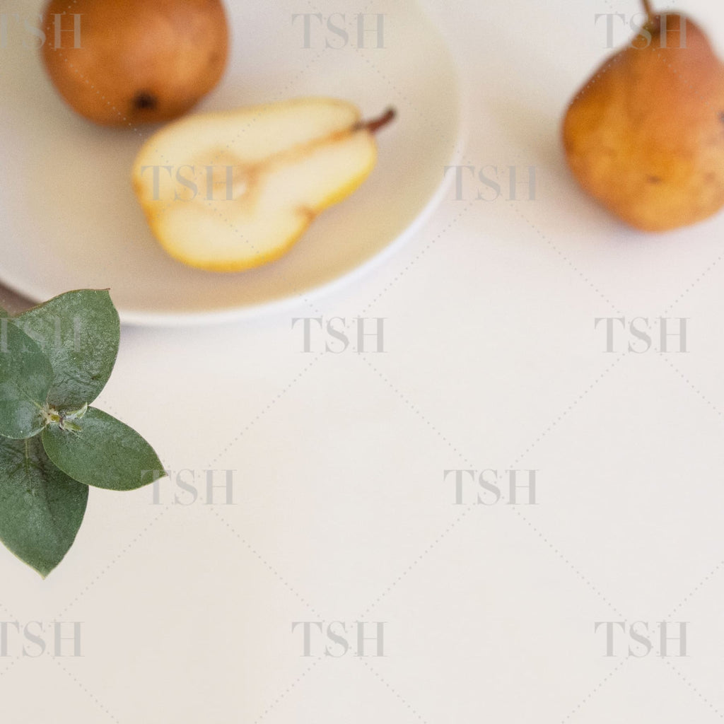 Fall harvest pears on white plate with eucalyptus on modern and minimalist white background