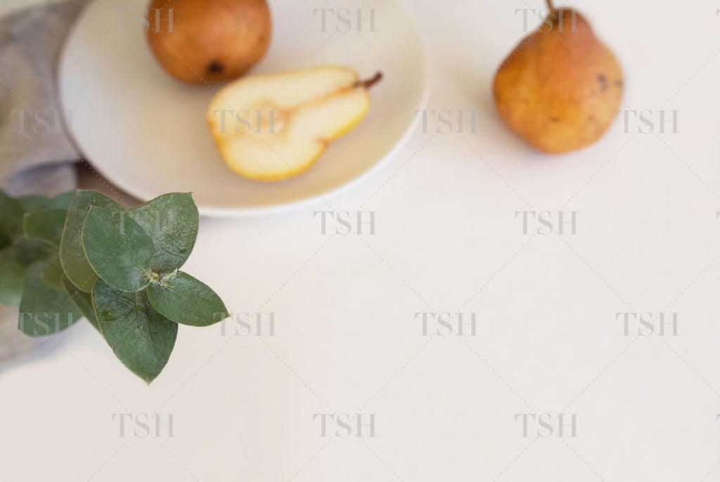 Fall harvest pears on white plate with eucalyptus and linen napkin on modern and minimalist white background