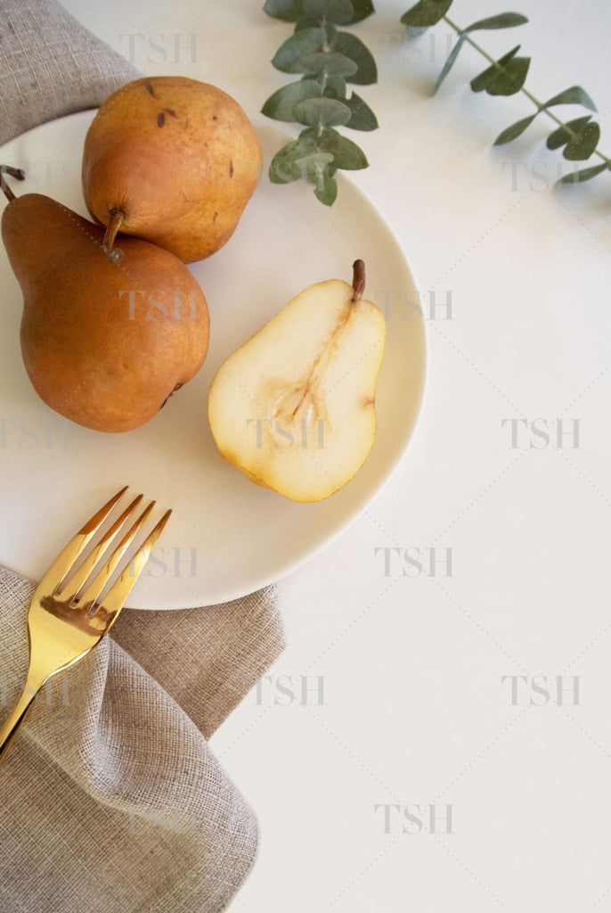 Fall harvest pears on white plate, eucalyptus, and linen napkin with gold fork