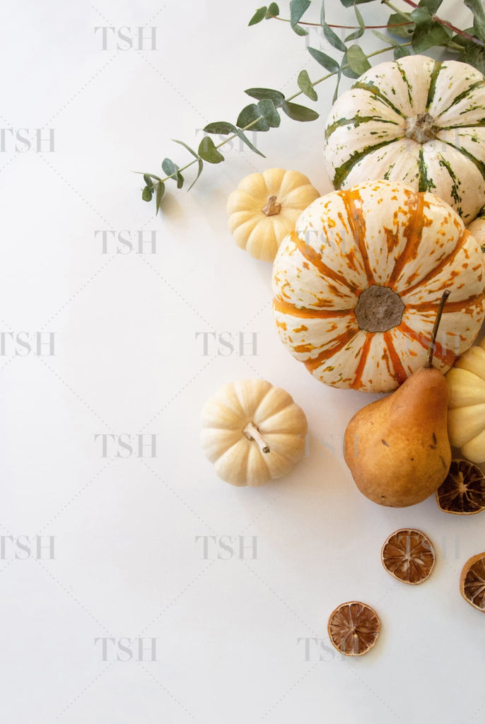 Colorful fall harvest pumpkins, eucalyptus, pears, and dried citrus