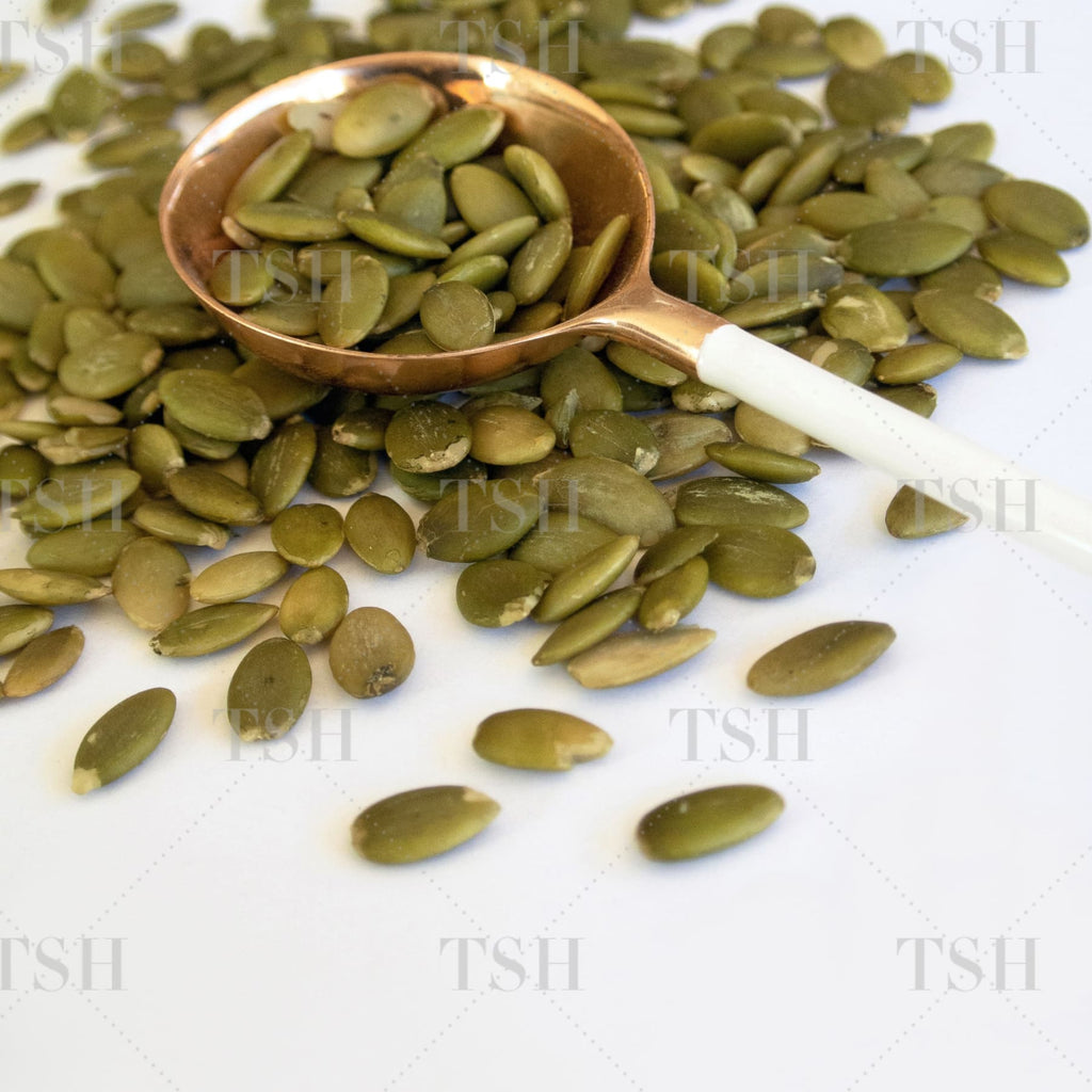Pumpkin seeds in copper measuring spoon with white background