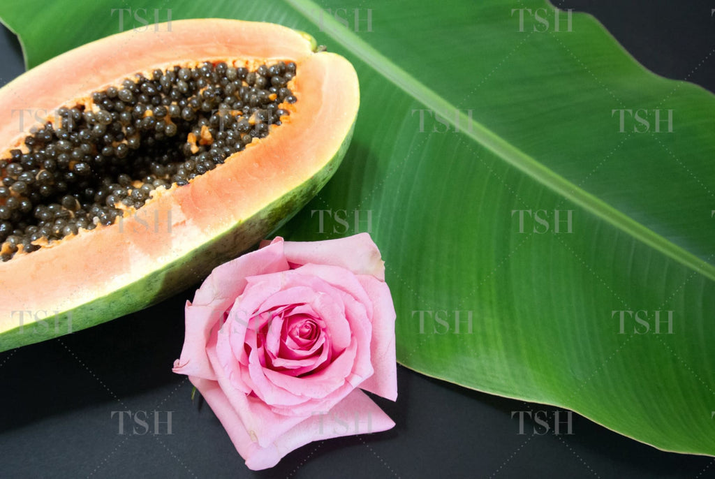 Tropical papaya fruit with banana leaf and pink rose on black background.