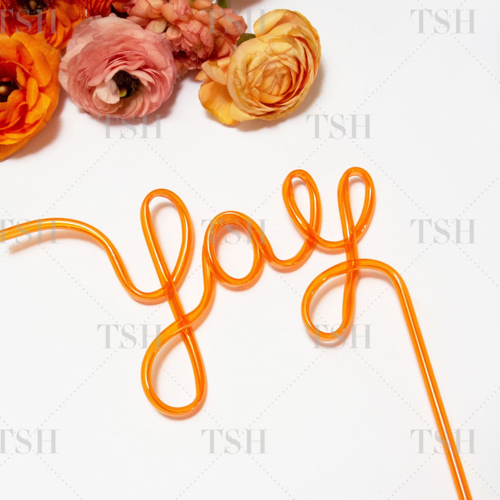 YAY Script orange party straw and spring flowers on white background.