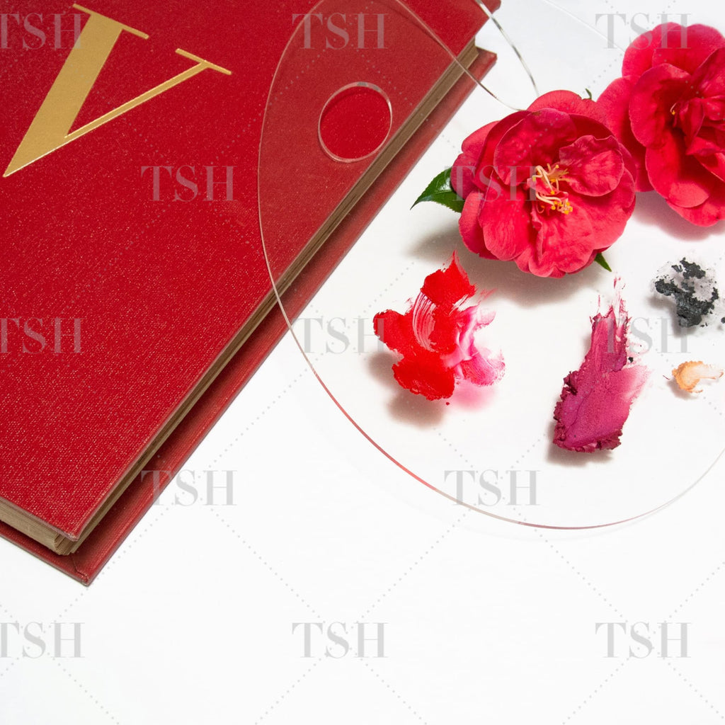 Red fashion book and artist's paint palette with abstract red and pink cosmetics and red camellia flowers on a white background.