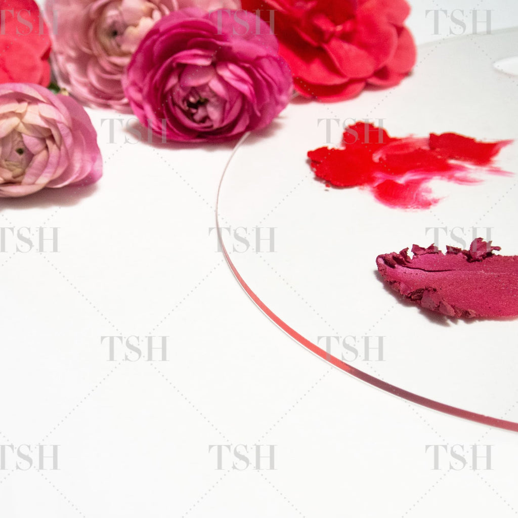 Acrylic artist's paint palette with abstract red and pink cosmetic brushstrokes, red camellia flowers, and pink ranunculus on a white background.