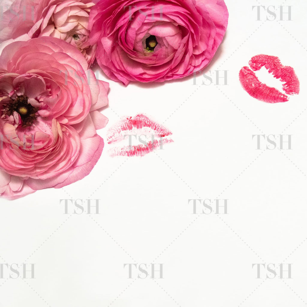 Feminine pink ranunculus flowers and pink lipstick kisses on a white background.