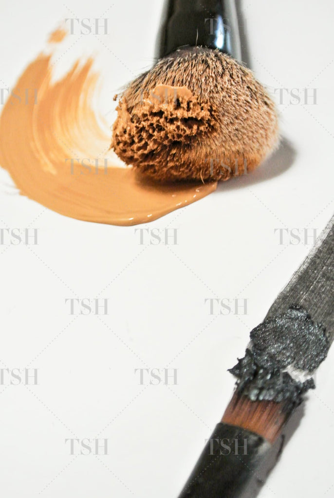 Beauty products and make up brushes create abstract brushstrokes with nude foundation and black eyeshadow.