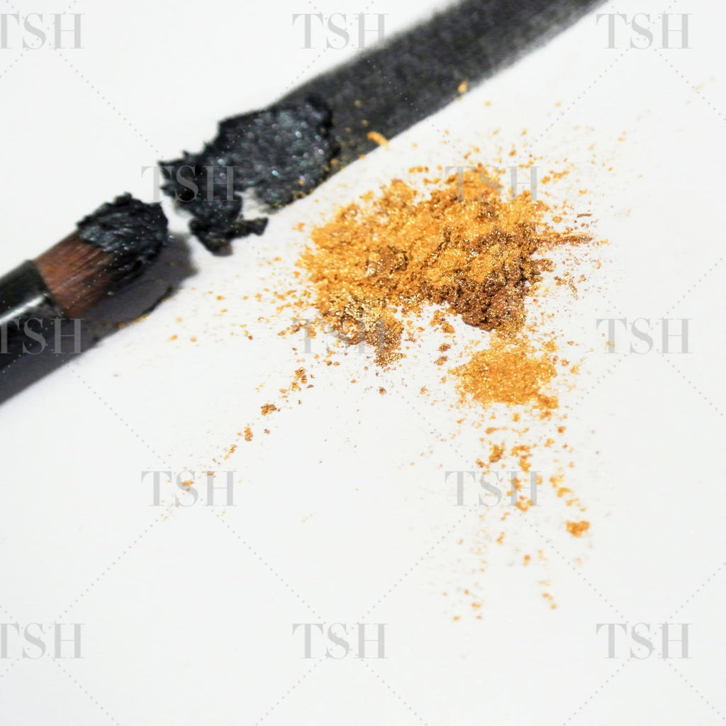 Beauty products and make up brushes create abstract brushstrokes with black eyeshadow and a metallic gold splash.