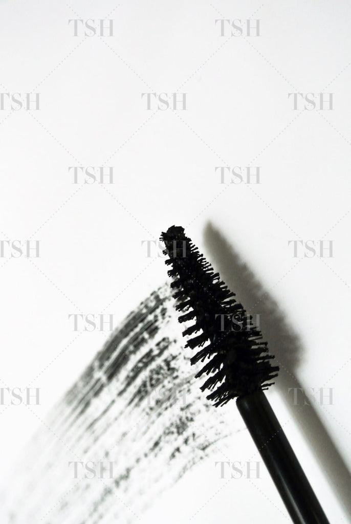 Black mascara brushstrokes with mascara wand on white background.