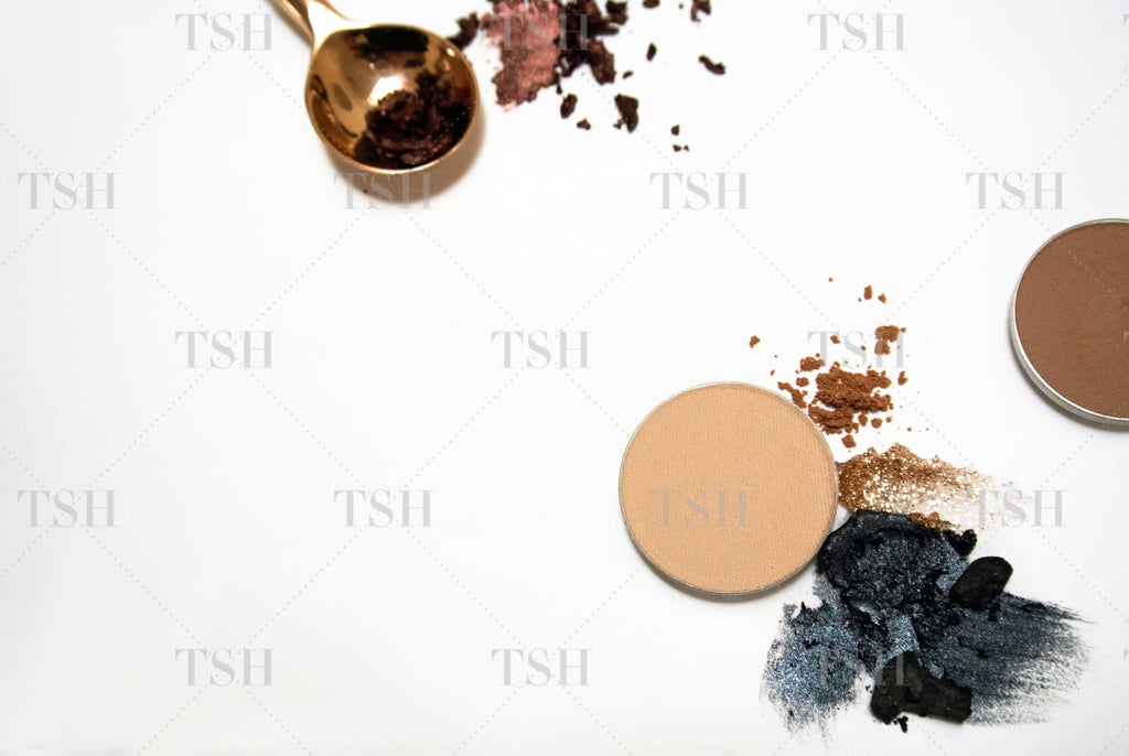 Abstract cosmetic brushstrokes with black, brown, and gold eyeshadow with round palettes of nude make up.
