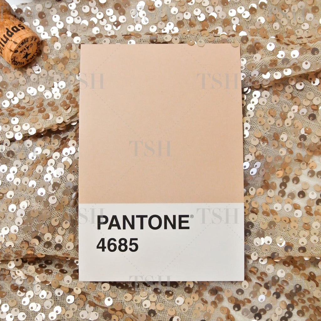 Pantone 4685 color palette swatch on sparkling neutral nude sequin textile background with champagne corks in black bowl.