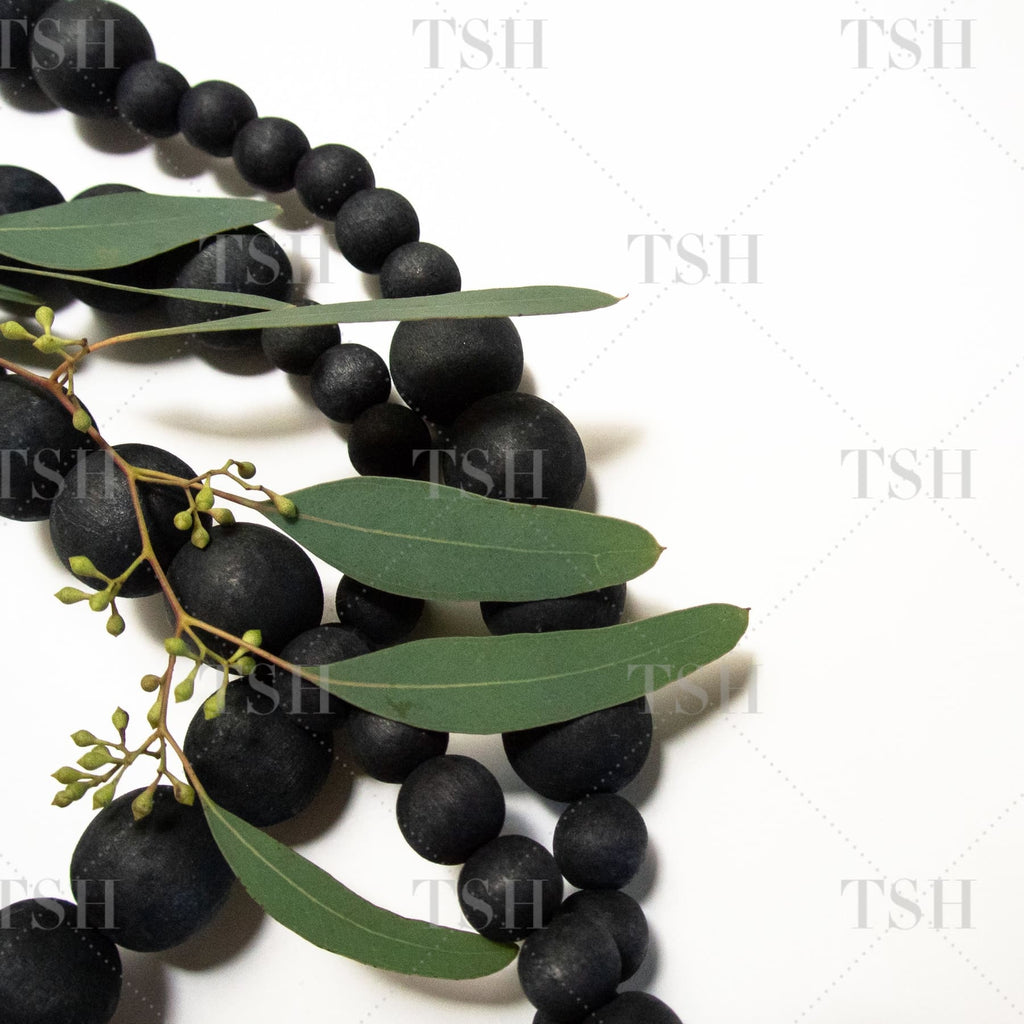 Decorative black beads with green eucalyptus leaves and foliage on white background.